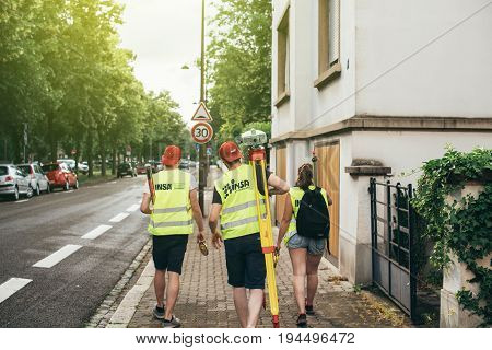 STRASBOURG FRANCE - MAY 30 2017: Students from the Institut National des Sciences Appliquees de Strasbourg performing a survey by theodolite for civil engineer checking surveyor equipment tachometer or theodolite outdoors at construction site in modern Fr