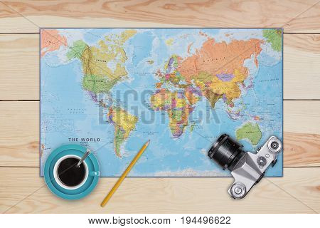 Map old camera cup of coffee and pencil laying on wooden desk. Necessary equipment of traveler or tourist. Top view of traveler baggage and retro camera with copy space. Travelling concept