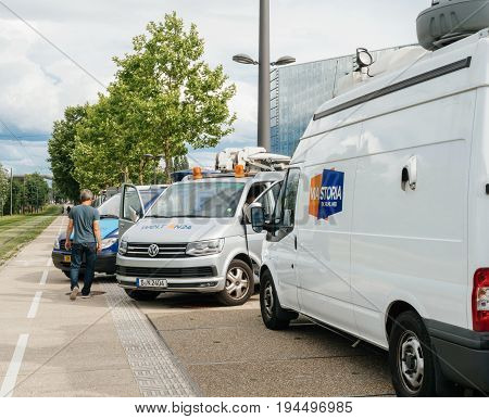 STRASBOURG FRANCE - JUN 30 2017: Engineer walking near TV Media Television Trucks with multiple Satellite parabolic antennas and fiber optic cables preparing to report live the official European Ceremony of Honor for Dr. Helmut Kohl at European Parliament
