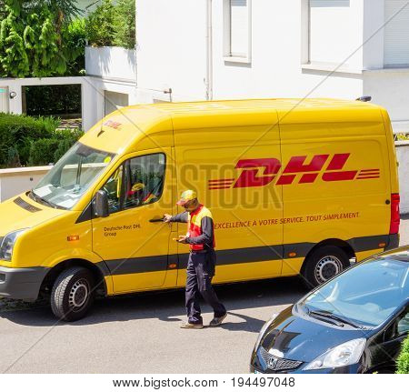 PARIS FRANCE - MAY 29 2017: Courier enters DHL yellow delivery van after delivering the on time delivering package parcel and looking in his smartphone communicator device where to deliver the next parcel