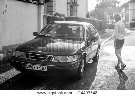 STRASBOURG FRANCE - MAY 2017: Woman walking toward her Saab 900 a compact luxury automobile which was produced by Saab from 1978 until 1998 in two generations beautiful sun flare light behind