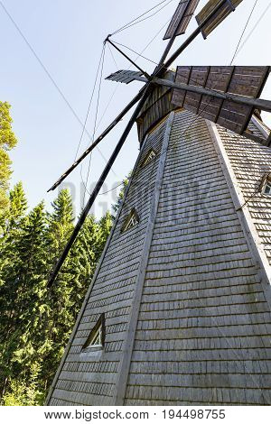 Ancient white wooden windmill with windows in forest in summer