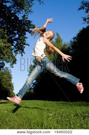 irl jumps in the park on a background of grass