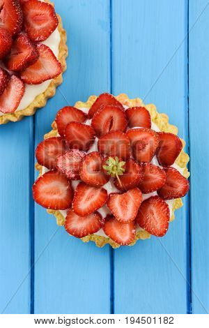 Tasty homemade tarts with fresh sweet strawberries and mascarpone cheese on blue table vertical with copyspace