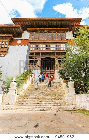 Paro Bhutan - September 10 2016: Low angle view of tourists standing on an old temple stairs. People waiting in front of the temple door for entrance.