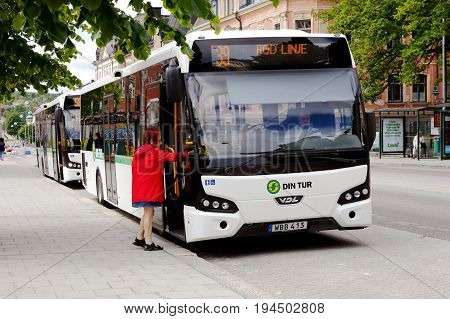 Harnosand Sweden - July 5 2017: An elderly woman with red clothes walks aboard the white city bus in traffic on line 39 for Min Tur at the bus stop City Hall.