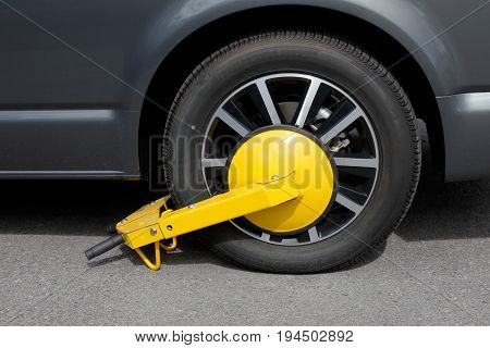 Harnosand Sweden - July 5 2017: One clamped car wheel with a yellow wheel clamp.