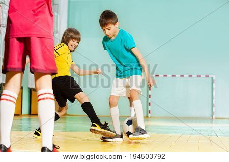 Portrait of happy preteen boys, football players, striking or passing the ball in school sports hall