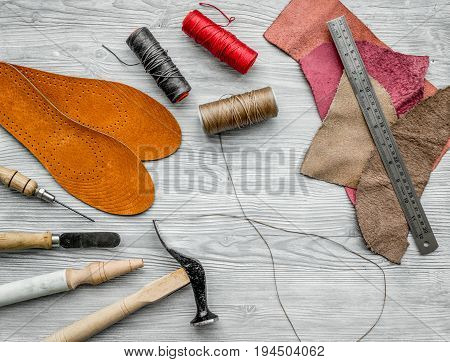 Working place of shoemaker. Skin and tools on grey wooden desk background top view.