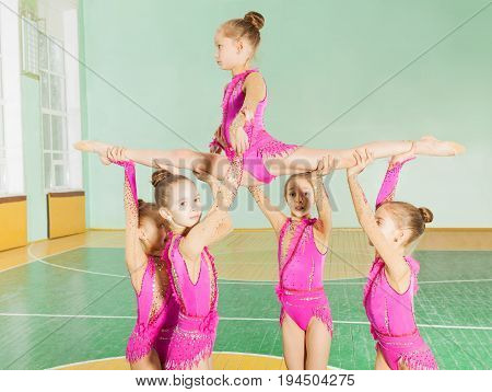Rhythmic gymnastics group of six preteen girls carrying out their routine in sports hall
