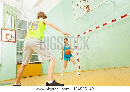 Portrait of teenage Asian girl dribbling the ball during the basketball match in school gymnasium