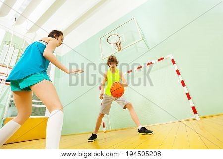 Low angle view of teenage boy dribbling basketball during the indoors match