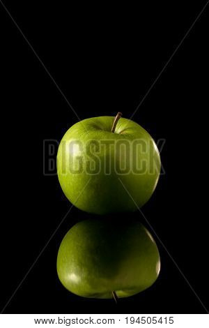 Green Apple On A Black Reflective Background