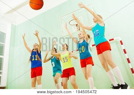 Female basketball team of five teenage girls defending the hoop during the championship in sports hall
