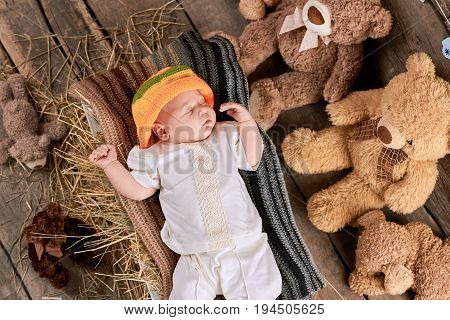 Sleeping baby and teddybears. Little kid on hay. The tight sleep.