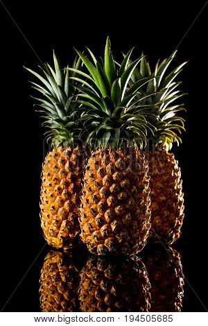 Three Pineapple On A Black Reflective Background