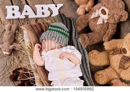 Sleeping child and teddybears. Little kid lying on straw.