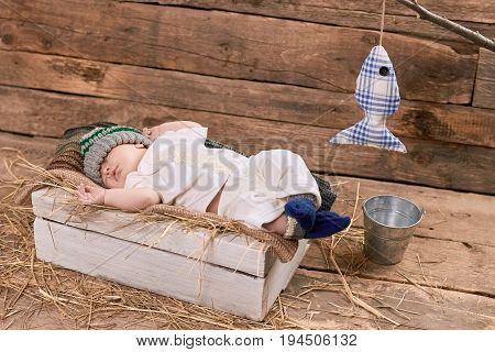 Baby fisherman sleeping. Child, wood and hay background. Tips for beginner fishermen.