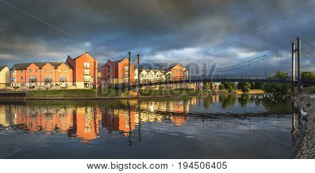 Houses on the waterfront in the city of Exeter. Sunset with a dramatic stormy sky. Devon. UK