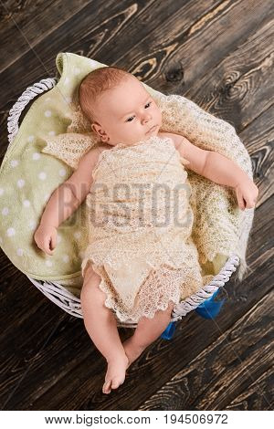 Basket with child, top view. Adorable caucasian infant boy.