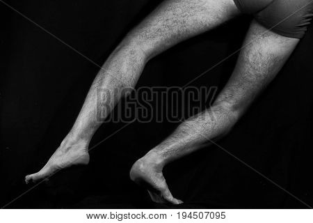 Beautiful muscular bare male feet on a black background. Classic high-contrast art photo