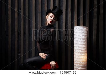 Woman Wearing  Top Hat Sits On  Chair  In A Dark Room
