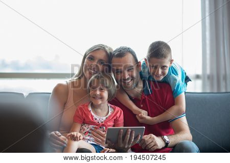 Happy Young Family Playing Together with tablet at home sitting on the sofa