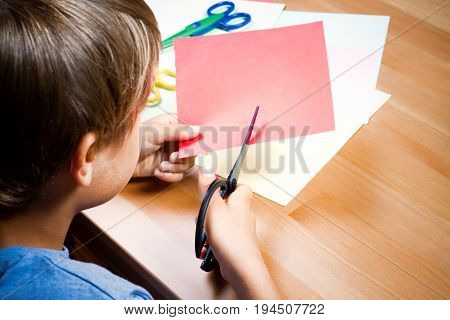 Child cutting colored red paper with scissors at the table