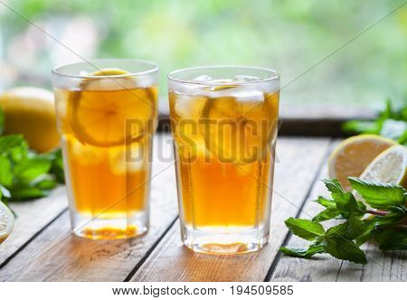 Ice tea with lemon slices on wooden table with a view to the terrace. Cold longdrink or lemonade. Close up summer vitamin antioxidant beverage. A frozen glass. Copy space for text.