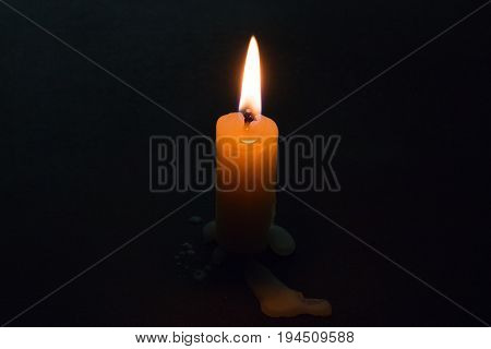 Burning candle on a black background closeup