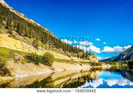 Reflections of blue sky, trees and mountains in the smooth surface on the crystal clear water of Crown Lake, along Highway 99 in Marble Canyon Provincial Park in British Columbia, Canada