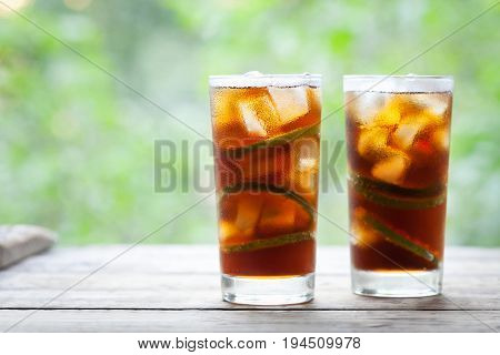 Cuba Libre or long island iced tea cocktail with strong drinks, cola, lime and ice in glass. Cold longdrink or lemonade. Close up summer beverage. Copy space for text.