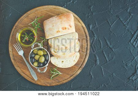 Mediterranean snacks set. Green and black olives olive oil herbs and sliced ciabatta bread on wooden board over dark stone background. Italian food concept. Top view. Copy space.