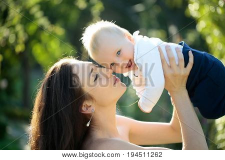 Happy cute baby boy small little son and pretty mother woman with long hair having fun smiling on sunny summer nature outdoors on natural background. Mothers day family love