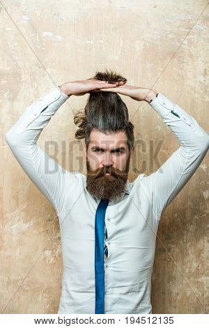 hairdresser. bearded man or hipster with long beard and raised hands on stylish hair on serious face in tie and white shirt on textured beige background