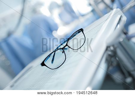Spectacles on the background of working surgeons.