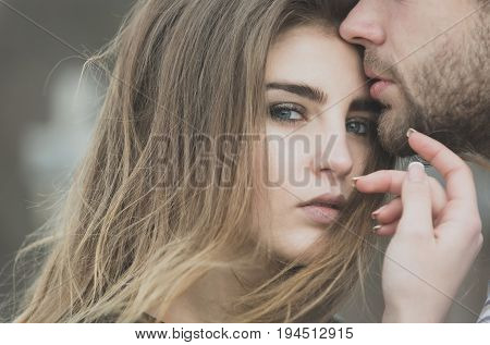 male lips with unshaven beard and moustache touching adorable face of pretty girl or cute woman with fashion makeup and stylish long hair on natural background. Love and tenderness