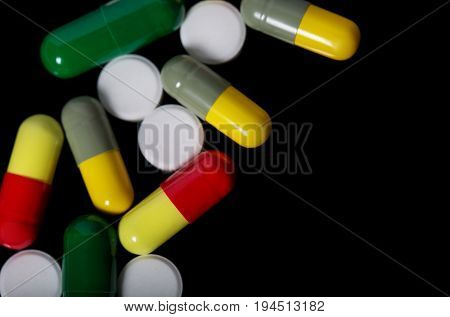 Assorted Pharmaceutical Medicine Pills, Tablets And Capsules Over Black Background