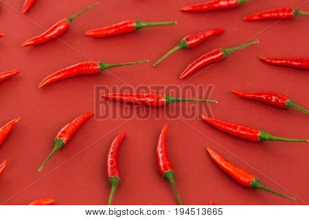 red hot chili peppers, popular spices concept - closeup on beautiful red hot chili peppers isolated on red background, green tails, collage of freely lying peppers, top view, flat lay