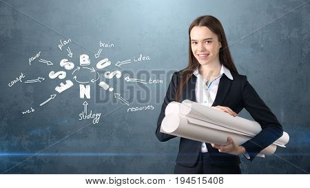 Woman In A Suit Near Wall With Blueprints And A Business Idea Sketch Drawn On It. Concept Of A Succe