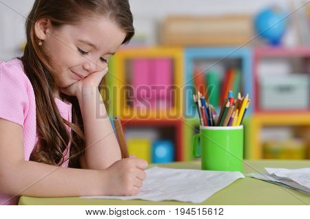 Cute little girl in pink shirt drawing in her room