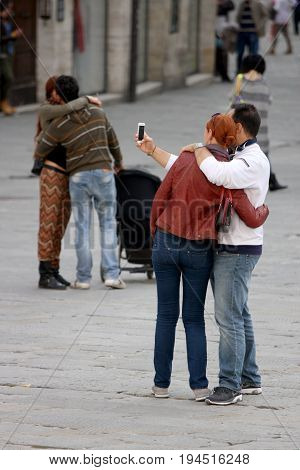 PERUGIA, ITALY. October 26, 2013: Two couples. one of the two hugging doing a selfie. the other kissing passionately in the city center of Perugia in Italy.