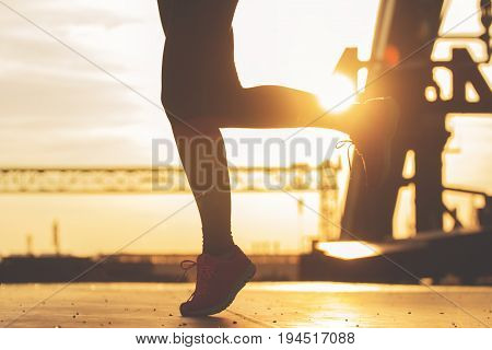 Jogging For A Healthy Life. Closeup Silhouette Of Attractive Sporty Woman Jogging On The Bridge Duri