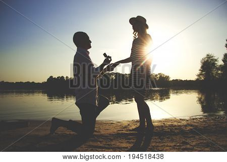 Will You Marry Me. Silhouette Of Young Man Staying On The Knee And Making Proposal For His Lovely Gi