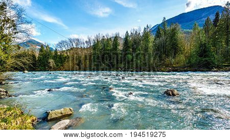 The fast flowing crystal clear waters of the Chilliwack River during early spring run off near the town of Chilliwack in British Columbia, Canada
