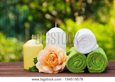 A stack of rolled towels candles and fragrant roses. Spa concept. Spa set in the summer garden.