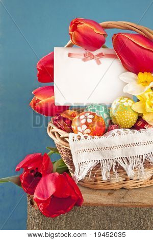 Postcard with a bow and Easter eggs on a background of spring flowers