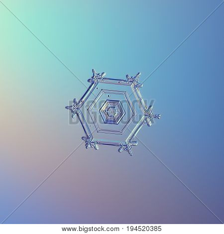 Real snowflake macro photo: small hexagonal plate snow crystal with simple internal structure, tiny arms and glossy relief centrel hexagon. Snowflake glitter on smooth blue background in cold light.