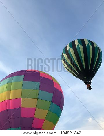 A pair of Hot Air Balloons with bright colors take to the blue skies in Prineville in Central Oregon on a beautiful summer morning.
