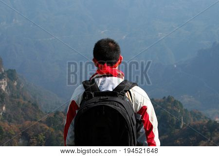 Chinese man standing on one of peaks of Wudang mountains